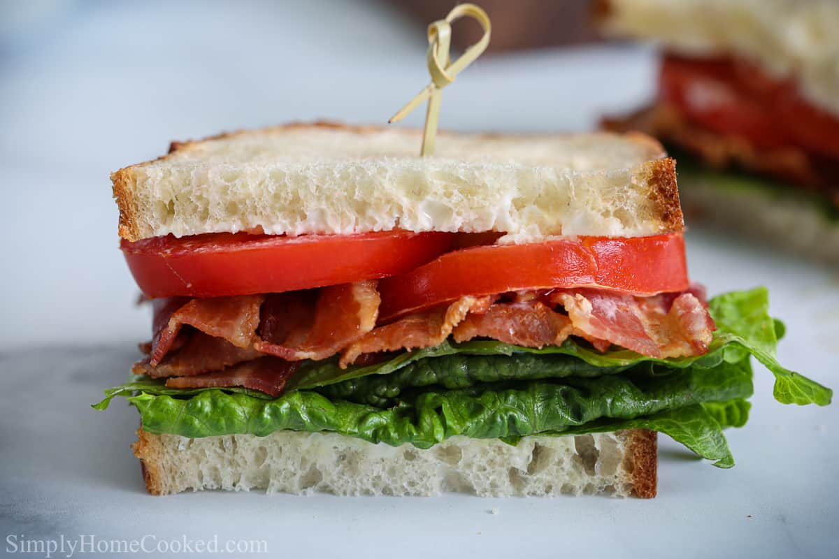 One half of a Classic BLT Sandwich with a toothpick through the top and with a white background.