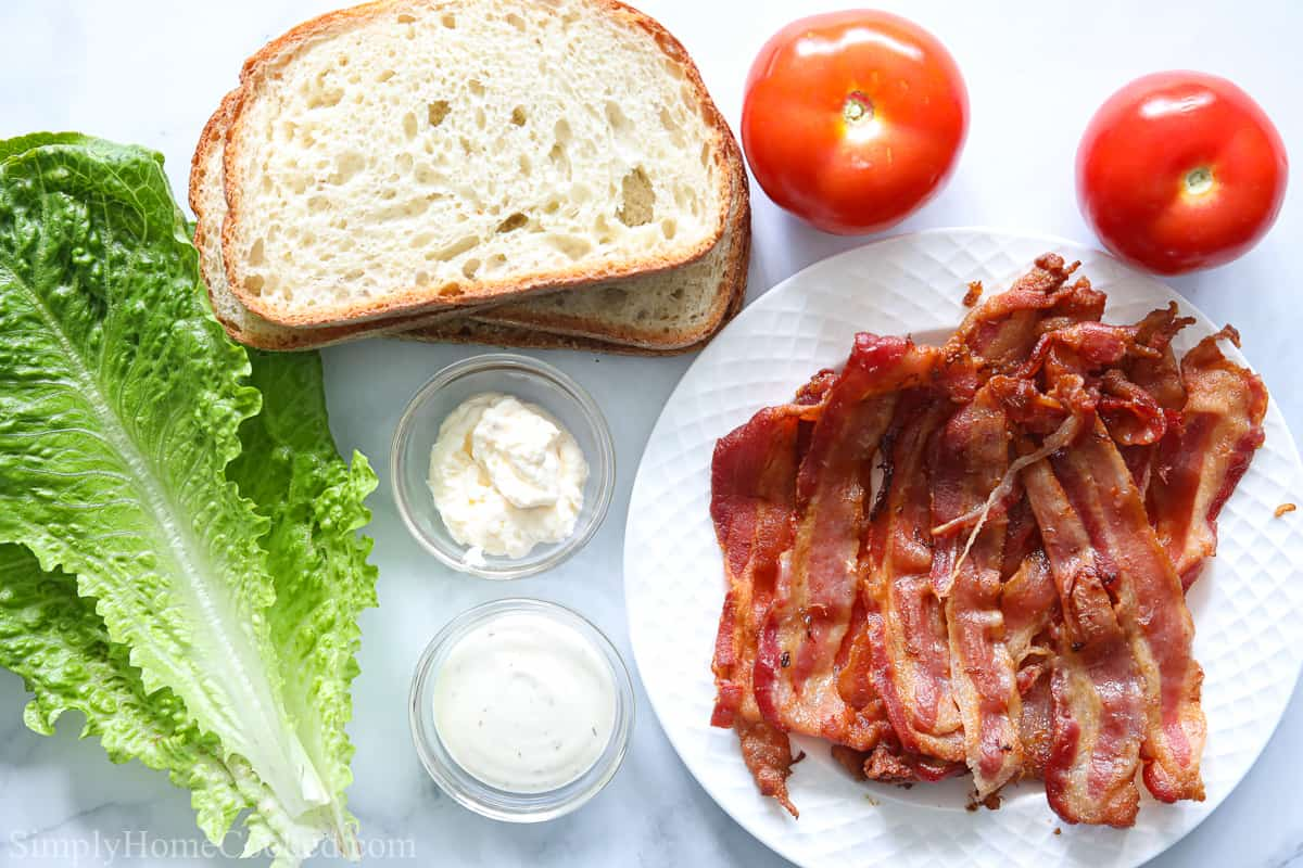 Ingredients for Classic BLT Sandwich, including rustic bread, tomatoes, bacon slices, romaine lettuce, ranch, and mayo on a white background.