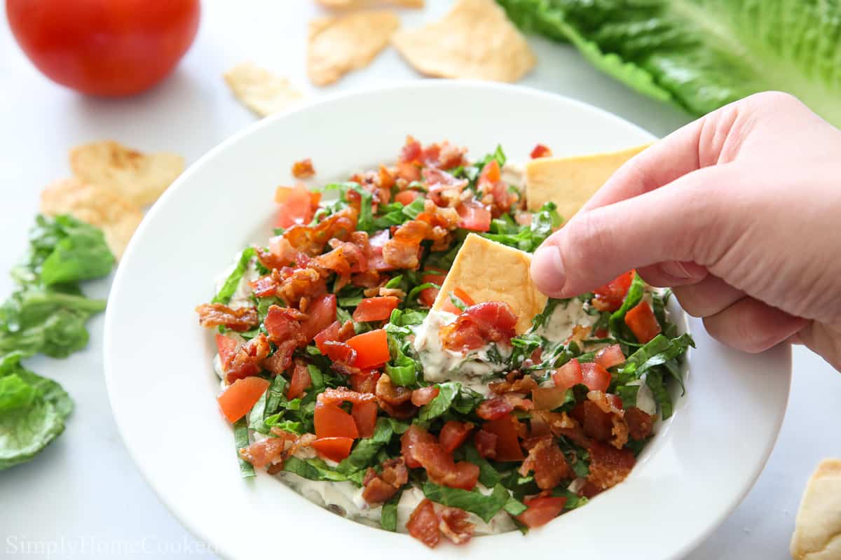 Dish of Easy BLT Dip with one chip scooping in and some more chips, lettuce, and tomato in the background