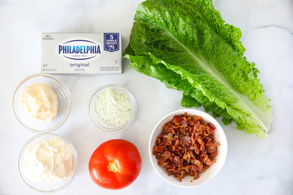 Ingredients for Easy BLT Dip, including cream cheese, sour cream, mayonnaise, romaine lettuce, tomato, chopped bacon, and ranch seasoning mix on a white background.