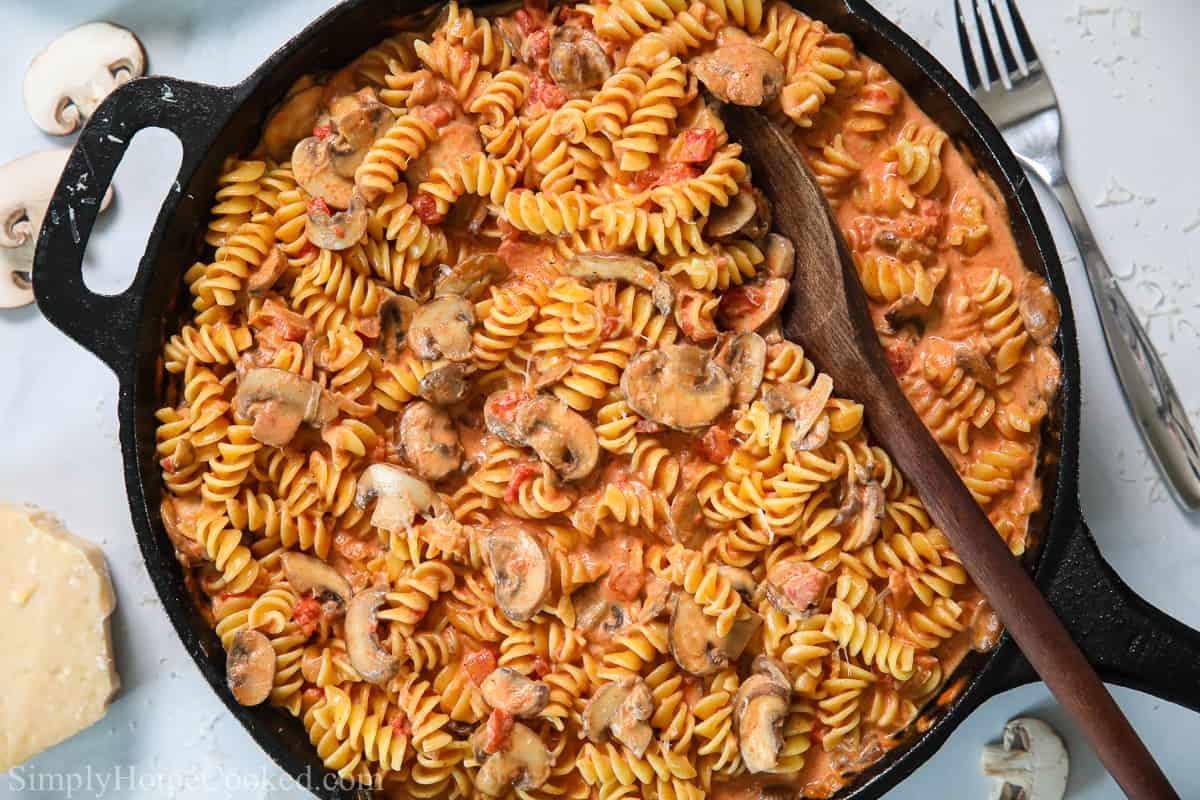 Skillet of Creamy Tomato and Mushroom Rotini Pasta with a wooden spoon in it and some sliced mushrooms, Parmesan, and a fork in the background.