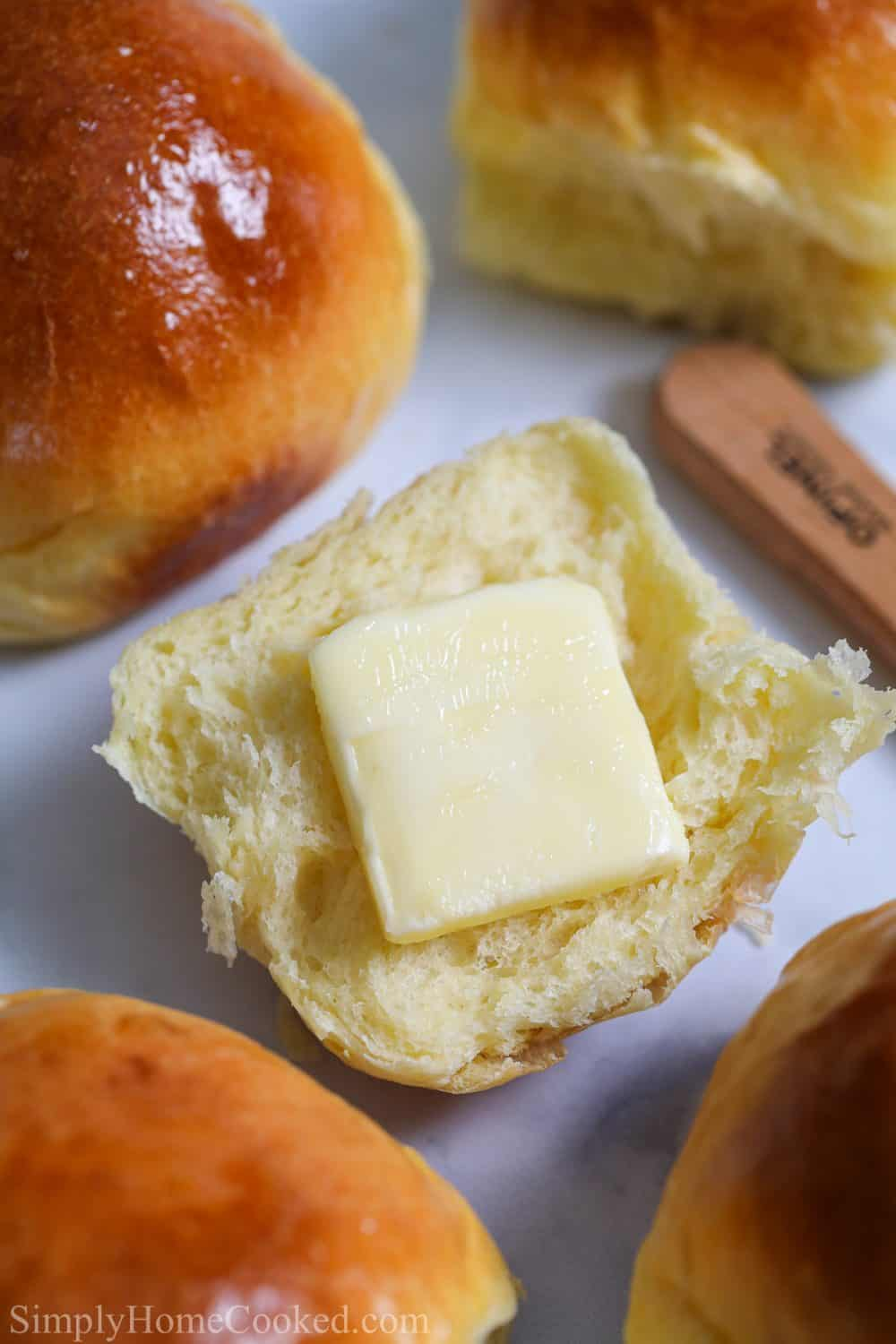 Soft Brioche Dinner Rolls with one cut in half with a pat of butter on it.