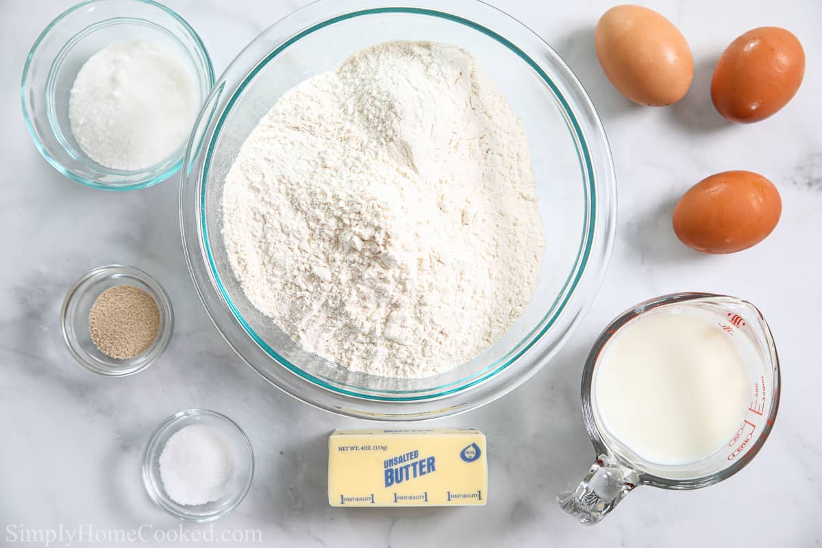 Ingredients for Soft Brioche Dinner Rolls, including flour, sugar, yeast, brown eggs, butter, milk, and salt on a white background.