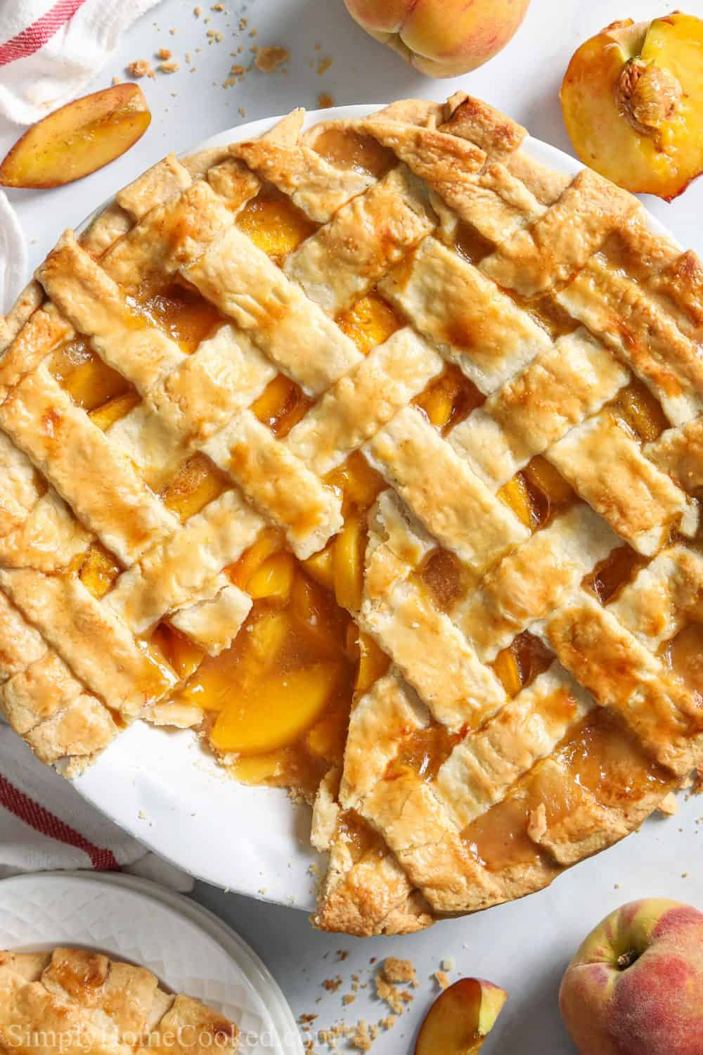 Perfect Peach Pie with a slice missing and peaches in the white background.