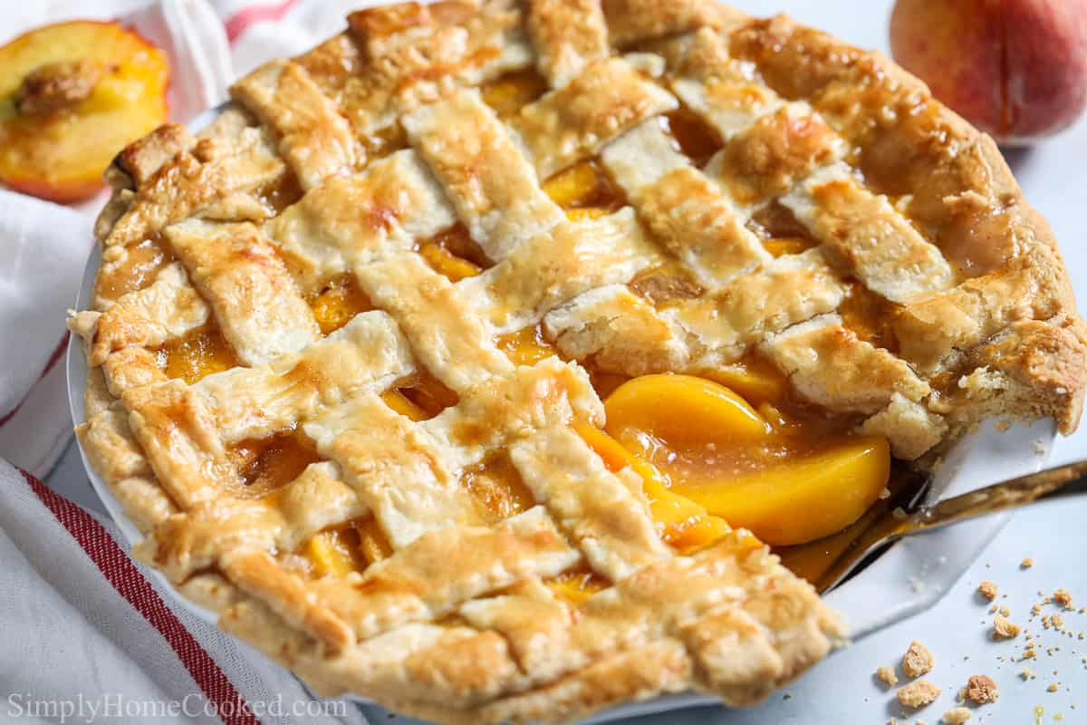 Close up of Perfect Peach Pie with a slice missing and a server in it, with peaches in the white background.