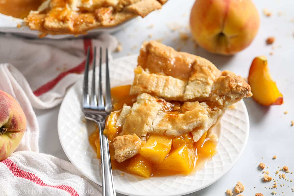 Slice of Perfect Peach Pie on a white plate with a fork and a pie and peaches in the background.
