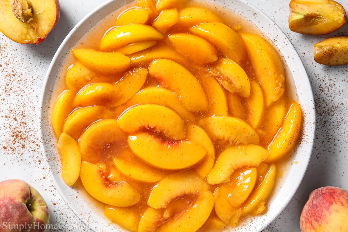 White bowl of Peach Pie Filling, with cinnamon and peaches nearby.