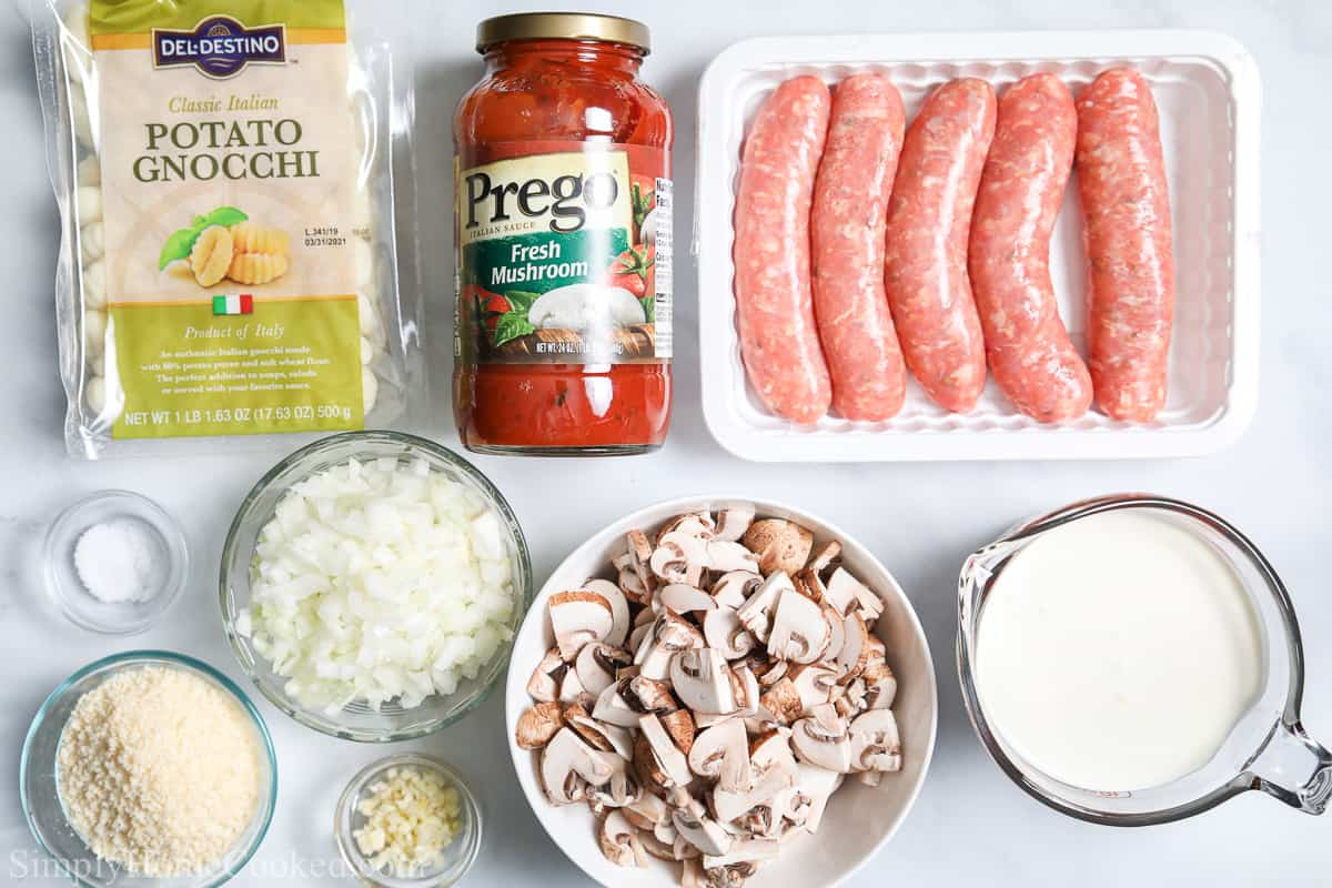 Ingredients for Creamy Tomato Gnocchi, including gnocchi, tomato sauce, chicken sausage, mushrooms, heavy cream, onion, garlic, salt, and Parmesan cheese.