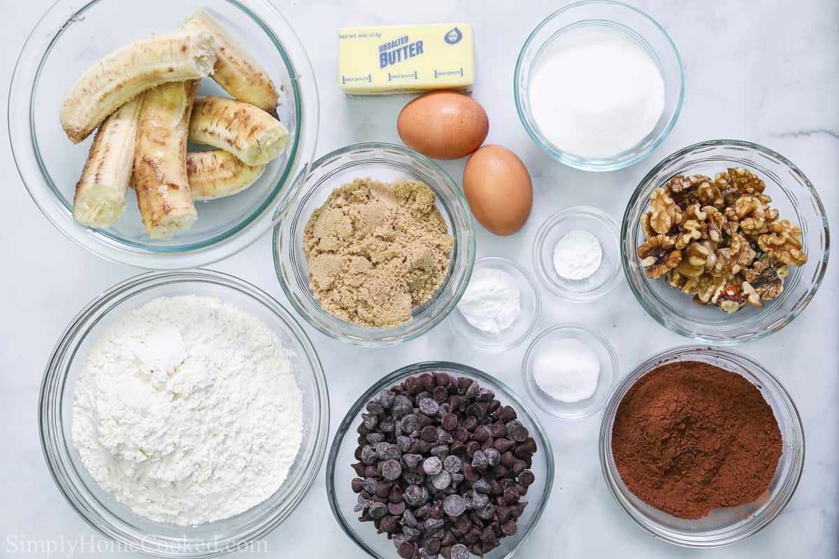 Ingredients for Double Chocolate Banana Bread recipe, including ripe bananas, butter , eggs, granulated sugar, grown sugar, flour, eggs, walnuts, cocoa powder, salt, baking powder, baking soda, and chocolate chips, on a white background.
