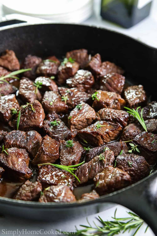 Close up of cast iron pan full of Garlic Herb Steak Bites with herb garnish.