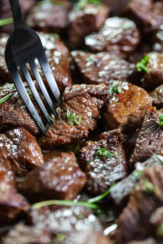 Close up of Garlic Herb Steak Bites with herb garnish and a fork piercing one steak bite.