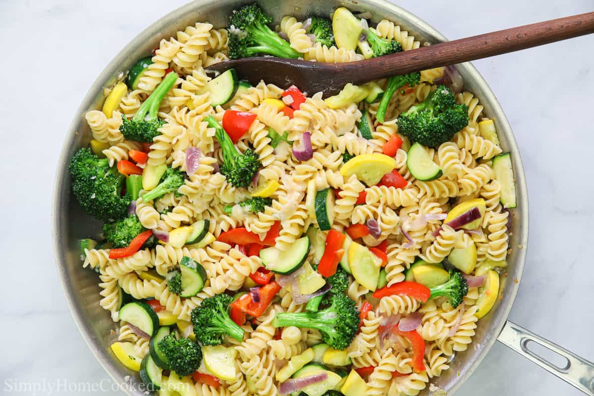 Easy Pasta Primavera in a pan with a wooden spoon.