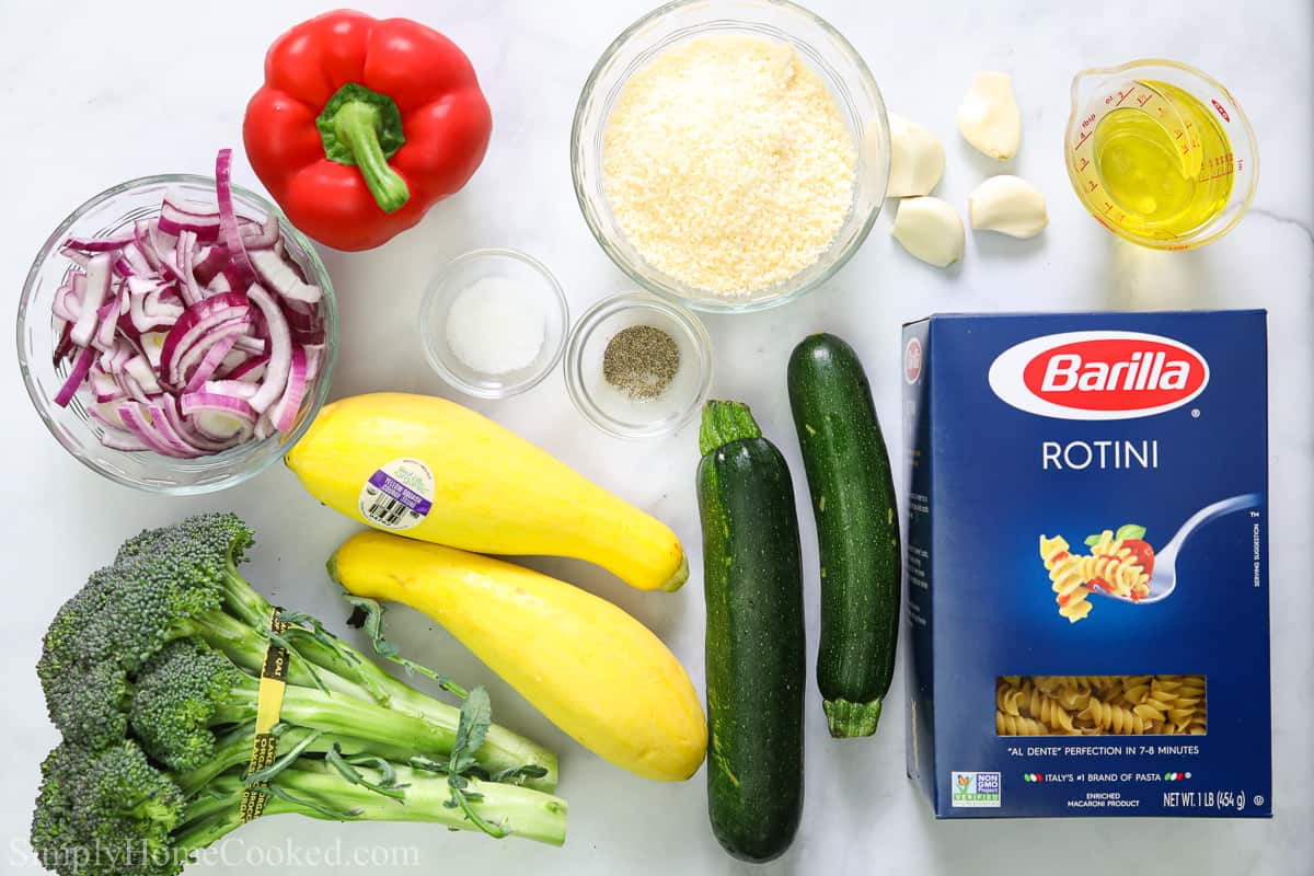 Ingredients for Easy Pasta Primavera, including bell pepper, squash, zucchini, box of rotini pasta, red onion, Parmesan cheese, garlic cloves, broccoli, salt, pepper, and olive oil.