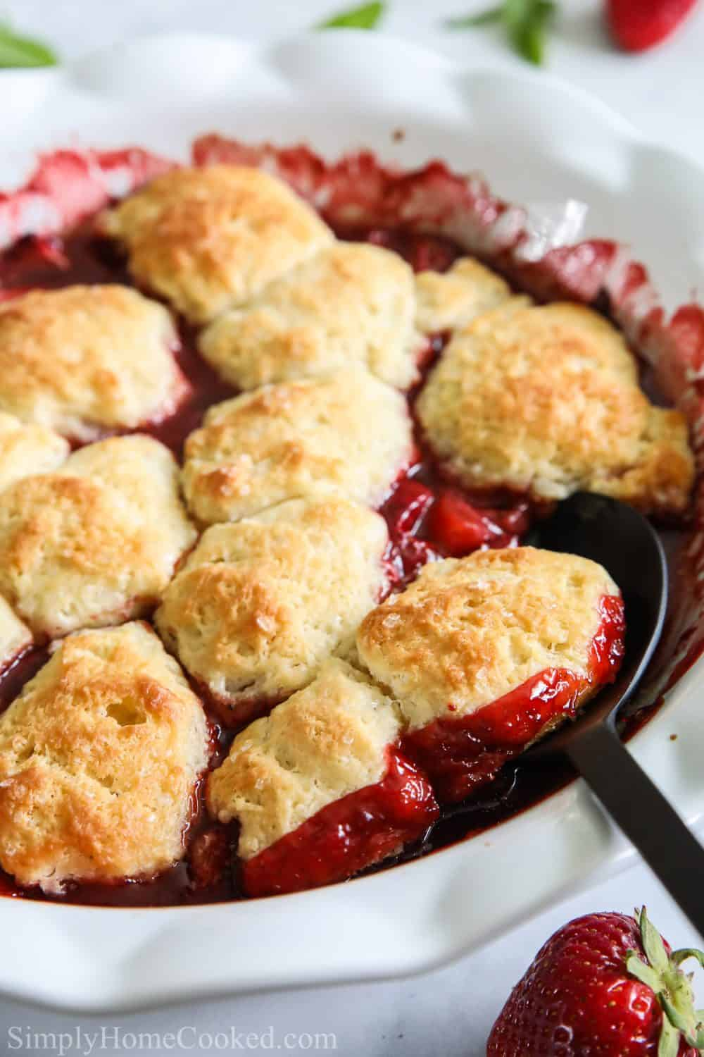 Close up of Strawberry Cobbler in a white pie dish with a serving spoon in it.
