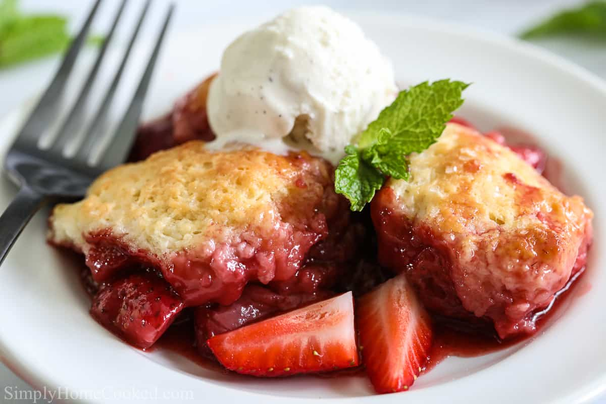 Close up of Strawberry Cobbler with a mint leave, scoop of ice cream, and a fork on a white plate.
