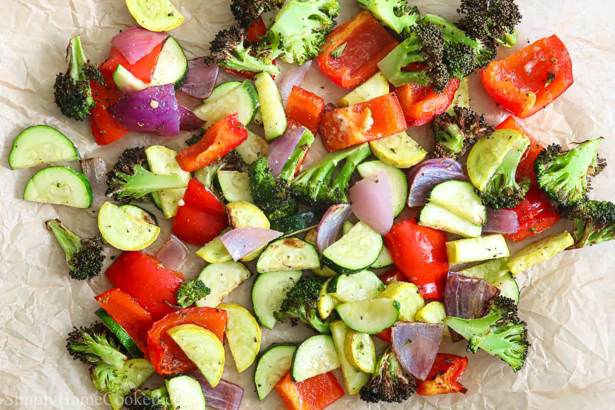 Roasted Air Fryer Vegetables, including red bell peppers, zucchini, squash, red onion, and broccoli, on a white background.