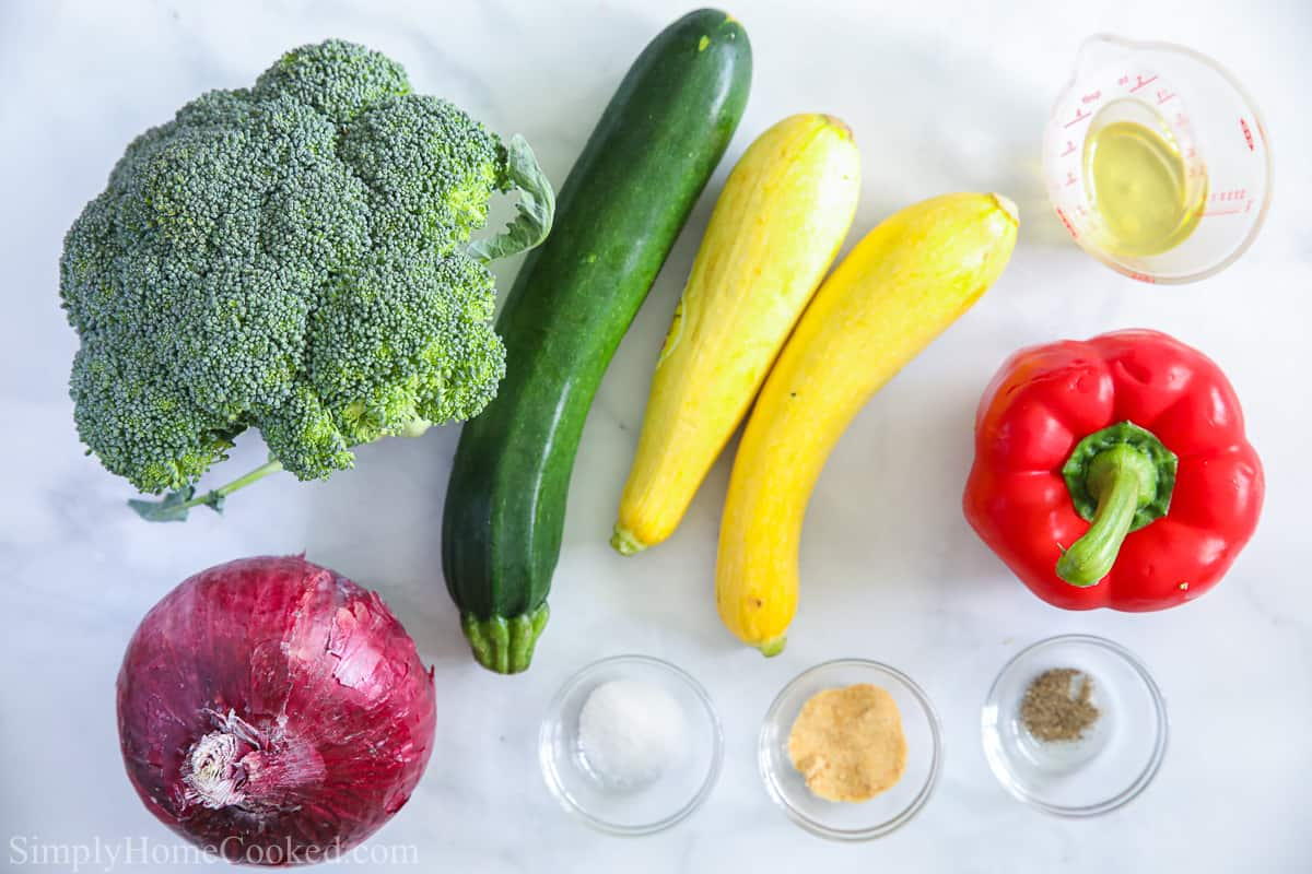 Ingredients for Roasted Air Fryer Vegetables, including broccoli, zucchini, squash, red onion, bell pepper, salt, pepper, garlic powder, and olive oil, on a white background.