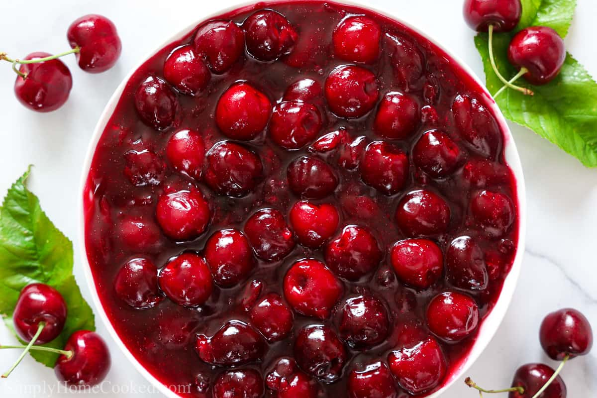 an overhead image of a plate filling with homemade cherry pie filling with fresh cherries and cherry leaves beside it.