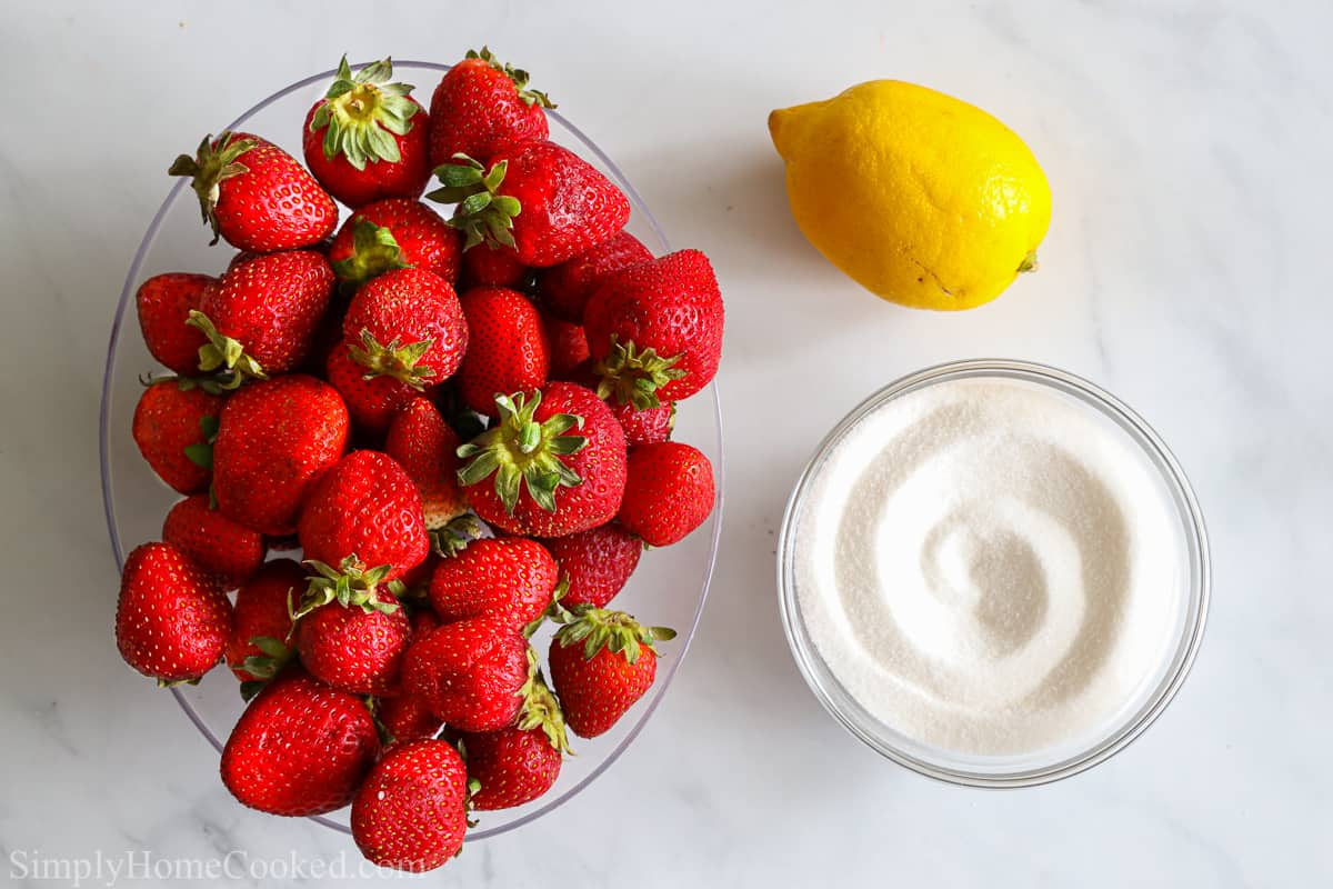 an overhead image of ingredients for strawberry jam on a white background