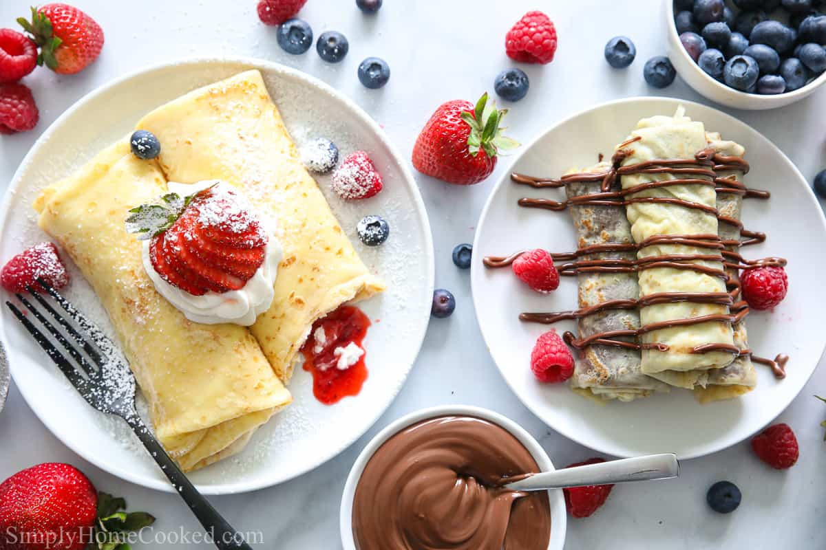 an overhead image of homemade strawberry crepes and Nutella crepes on a white background with berries scattered next to them.