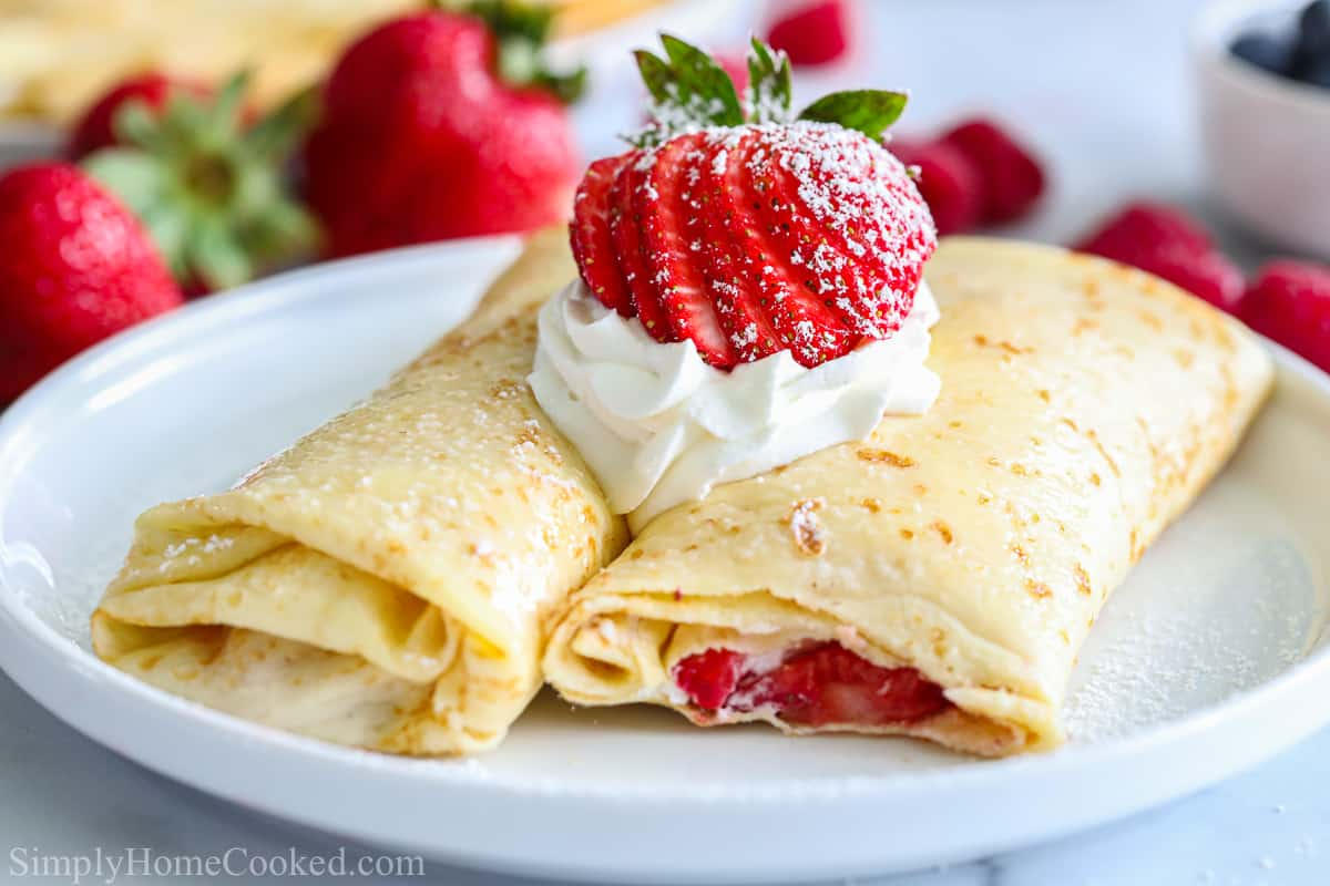 a close up image of crepes filled with strawberries and whipped cream on a white plate with a strawberry, whipped cream, and powdered sugar on top.
