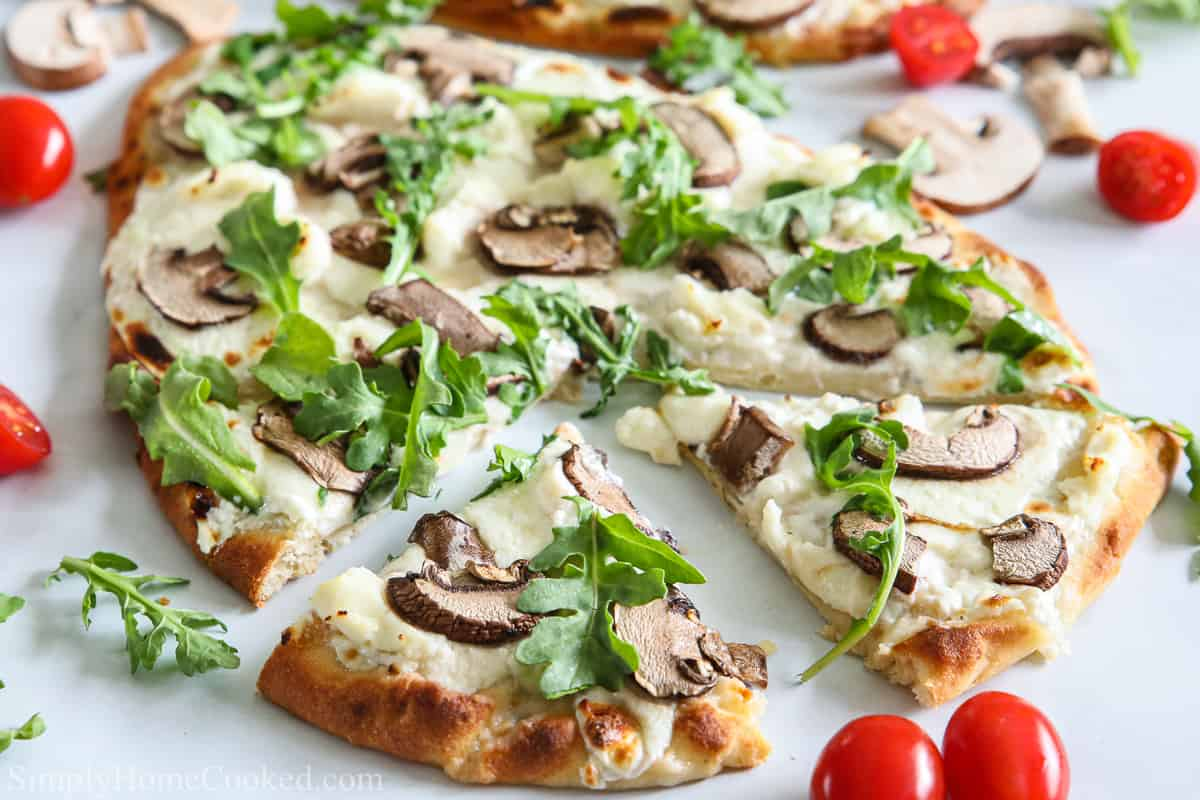 Close up of Mushroom Arugula Flatbread Pizza, sliced, with cherry tomatoes and other ingredients scattered on a white background.