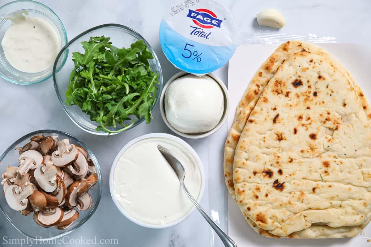 Ingredients for Mushroom Arugula Flatbread Pizza, including naan, Greek yogurt, ranch dressing, mozzarella, ricotta, garlic, arugula, and mushrooms.