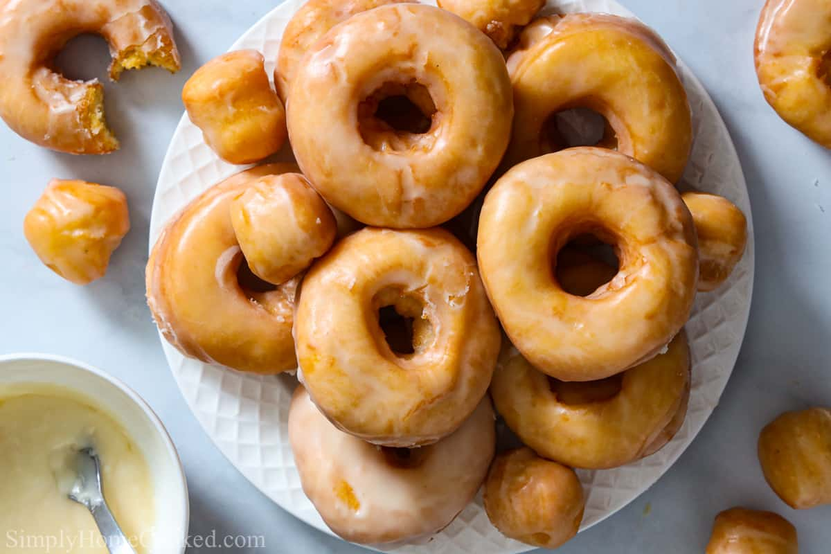 Plate holding a pile of Old Fashioned Sour Cream Donuts, with some more on the side with a bowl of glaze.