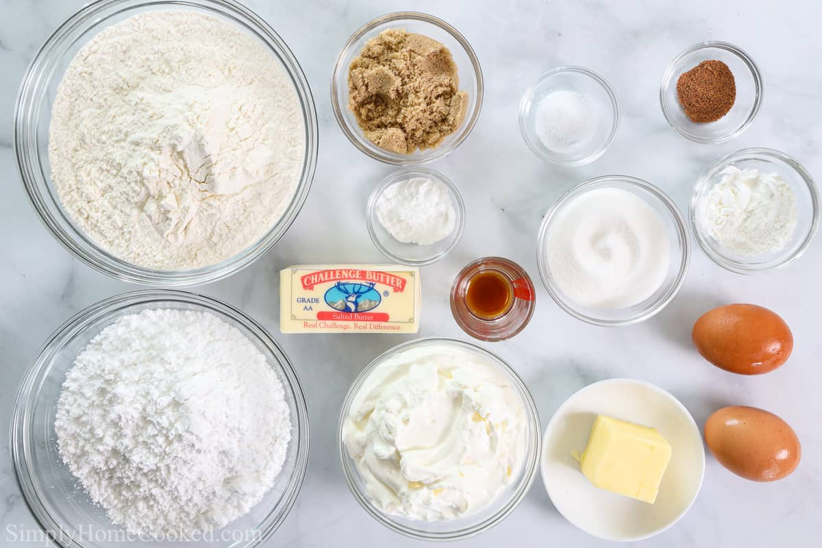 Ingredients for Old Fashioned Sour Cream Donuts, including flour, sugar, brown sugar, butter, cornstarch, baking powder, salt, nutmeg, sour cream, vanilla extract, eggs, and powdered sugar for the glaze.