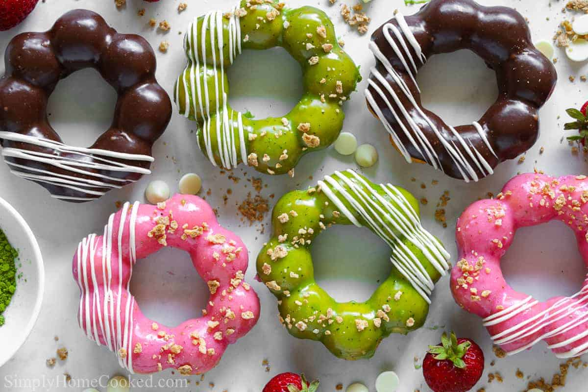 an overhead image of homemade pon de ring mochi donuts on a white background