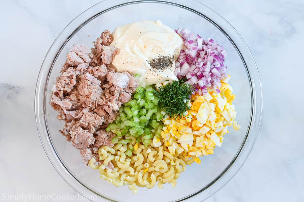 Clear bowl of ingredients for the Best Tuna Pasta Salad, including mayonnaise, hard-boiled eggs, tuna, onion, celery, dill, salt, pepper, and elbow macaroni on a white background.