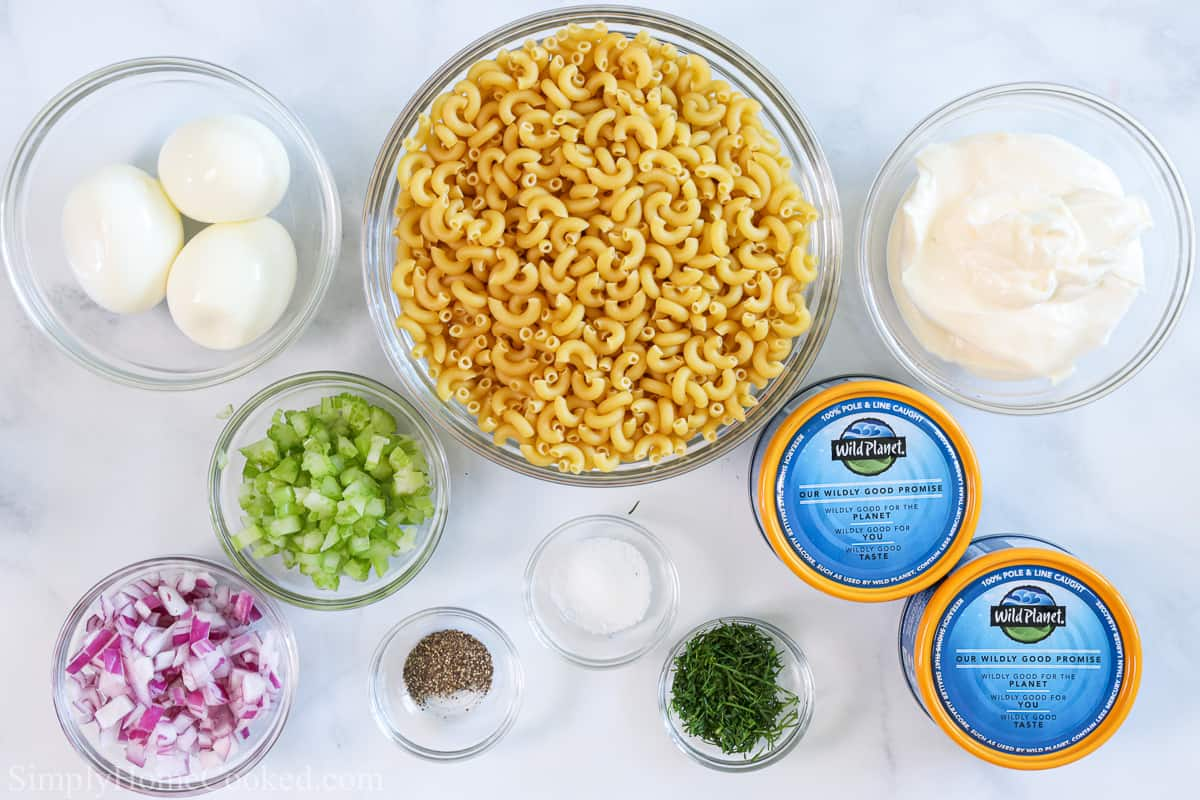 Ingredients for the Best Tuna Pasta Salad, including hard-boiled eggs, elbow macaroni, chopped onion, celery, and dill, mayonnaise, salt, pepper, and albacore tuna on a white background.