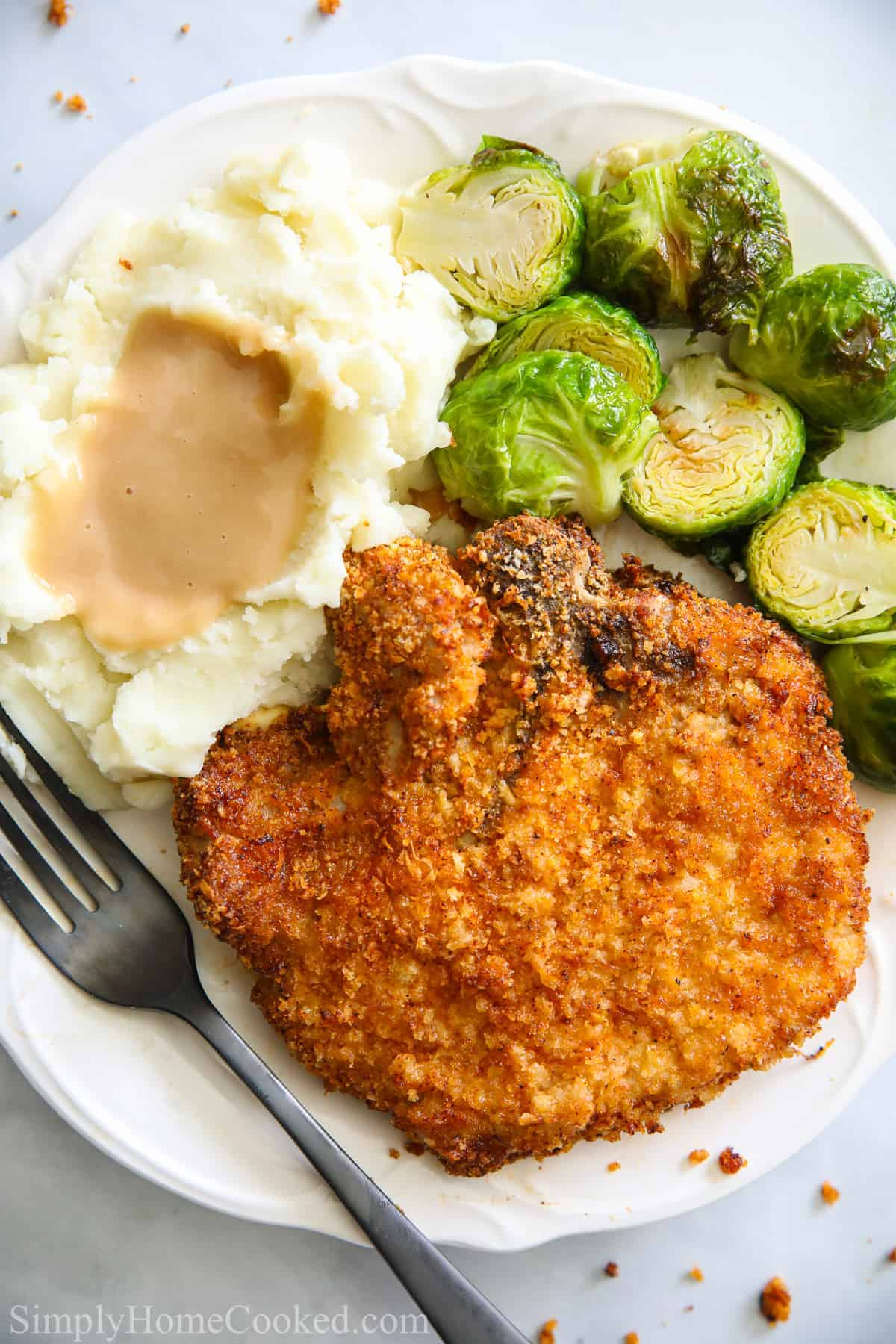 Plate with Juicy Air Fryer Pork Chops, brussels sprouts, and mashed potatoes and gravy, with a fork.