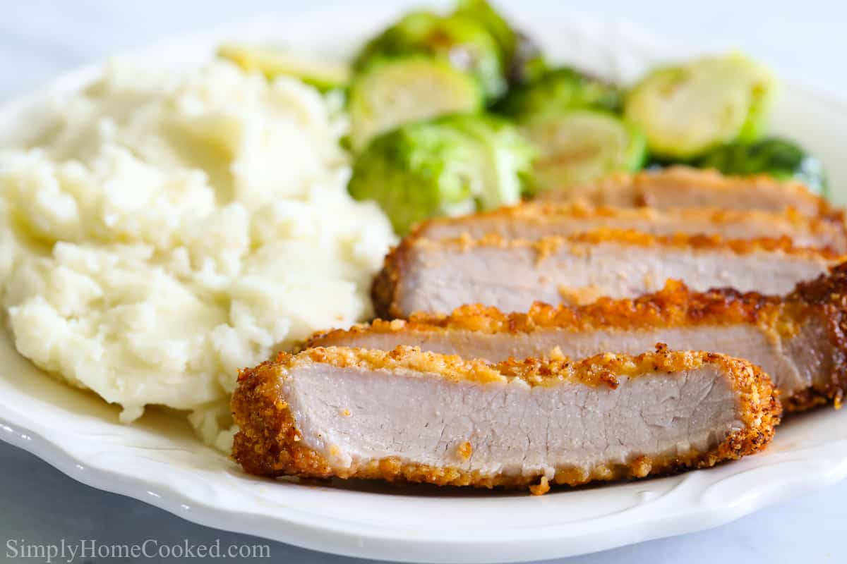Sliced Air Fryer Pork Chops with brussels sprouts and mashed potatoes on a plate.