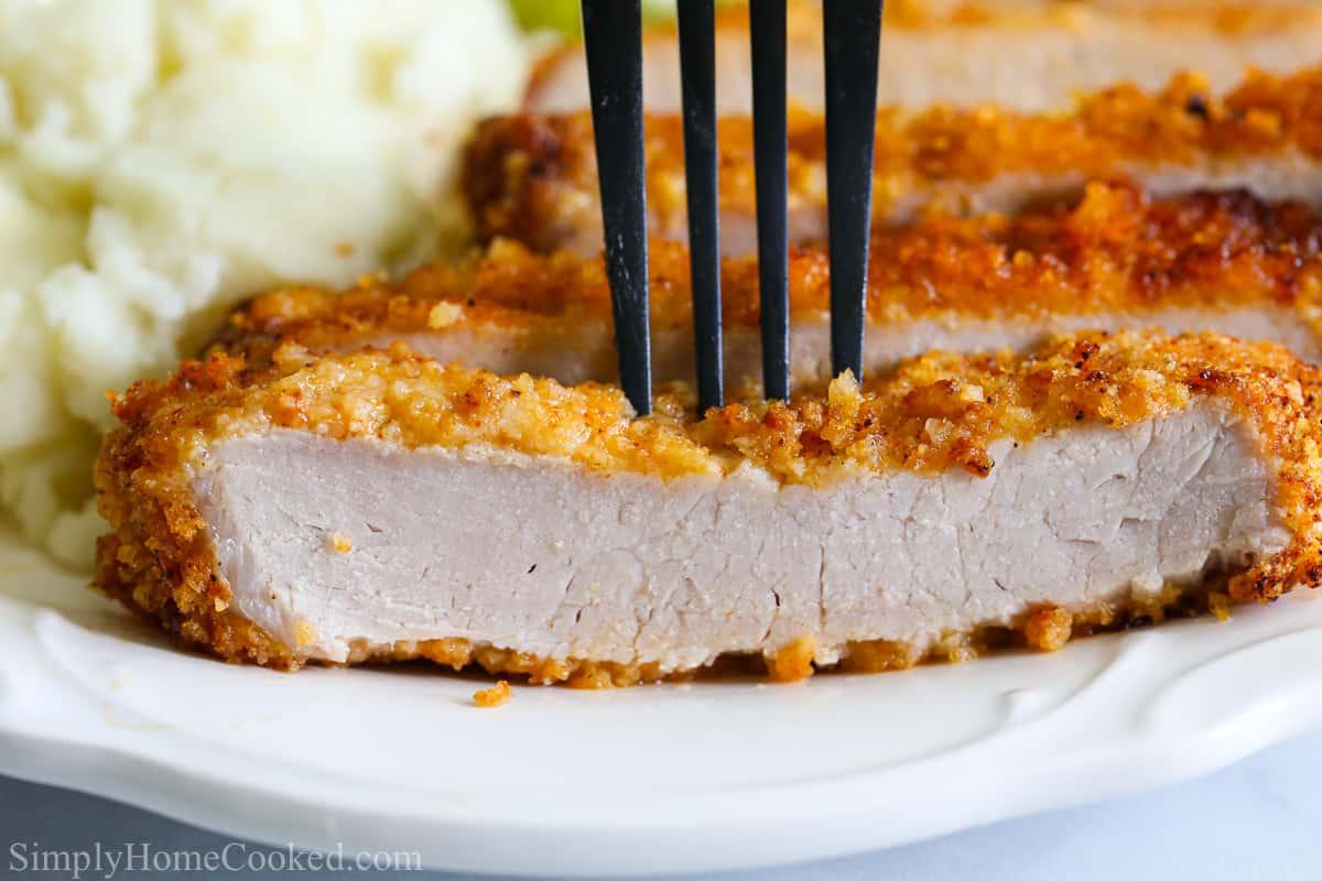 Close up of fork in slice of Juicy Air Fryer Pork Chop.