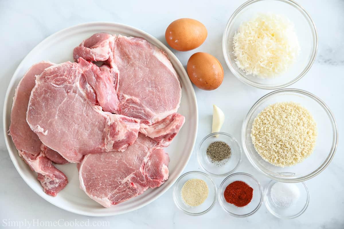 Ingredients for Juicy Air Fryer Pork Chops, including bone in pork chops, eggs, Parmesan cheese, Panko breadcrumbs, garlic clove, paprika, onion powder, salt, and pepper, on a white background.