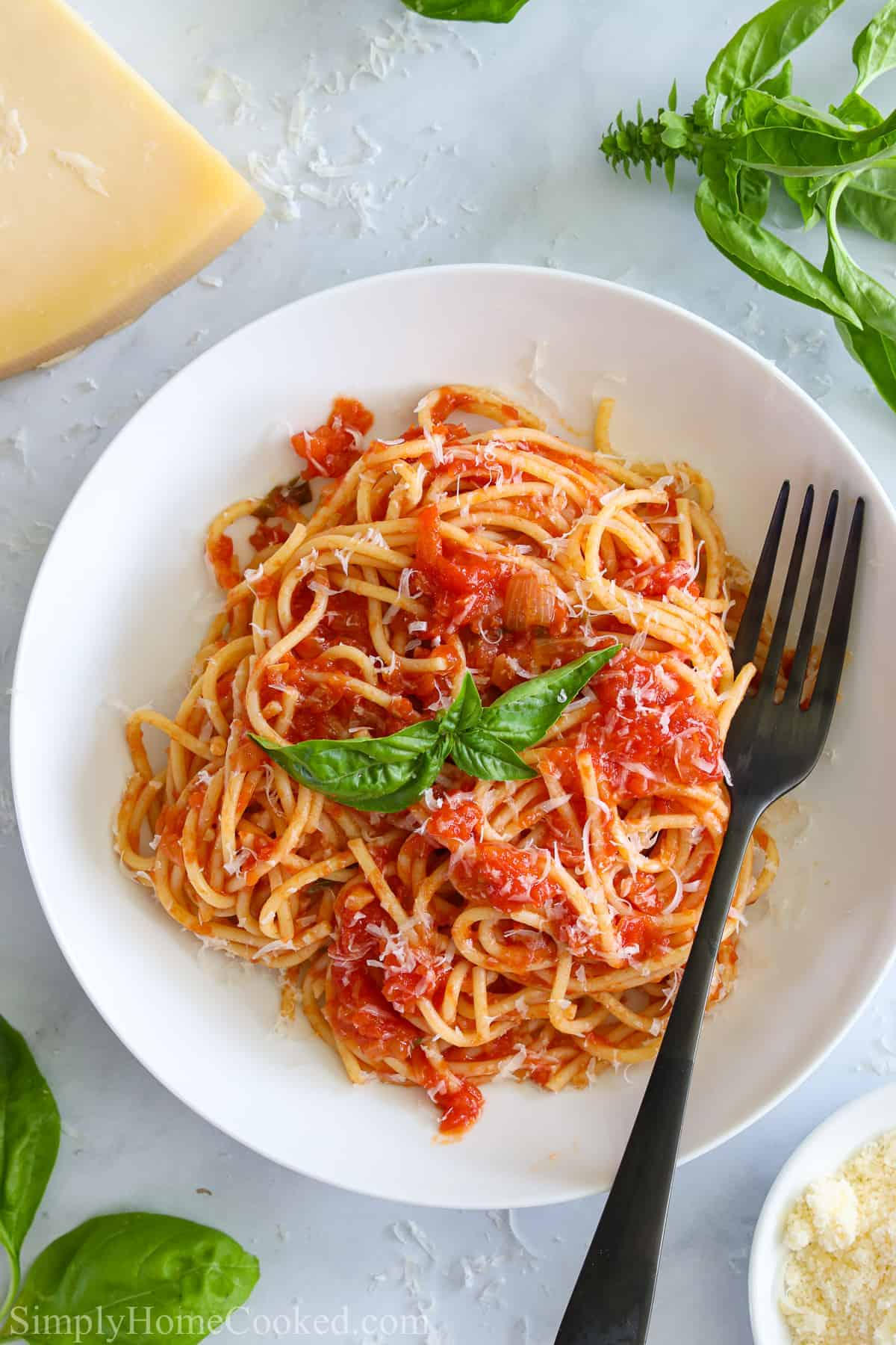Pasta Pomodoro on a white plate with a fork and Parmesan cheese and basil nearby.