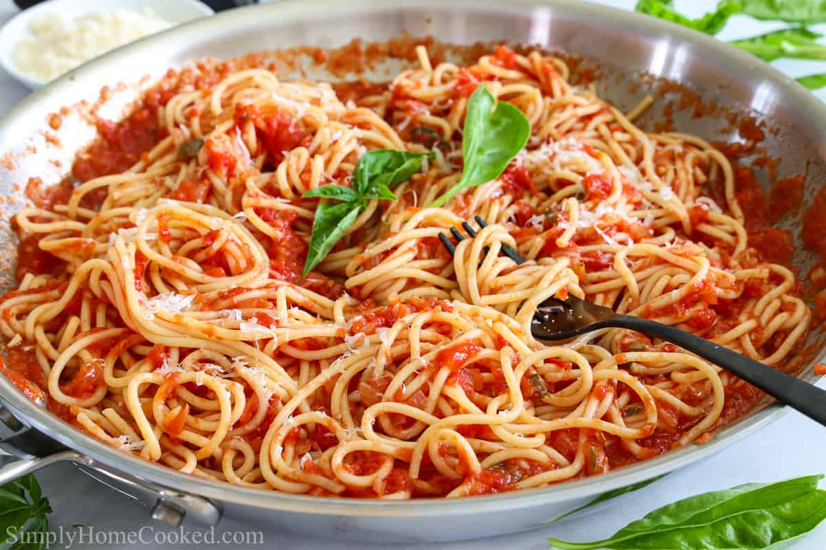 Pan of Pasta Pomodoro with a fork twirling the pasta and basil leaves on top and to the side.