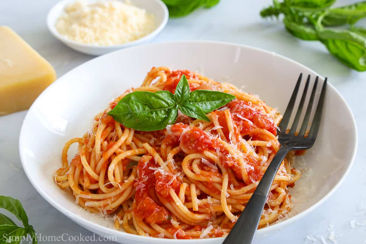 Plate of Pasta Pomodoro with a fork and basil leaves, and Parmesan cheese and basil in the background.
