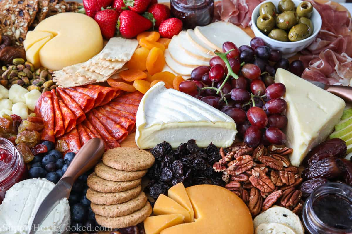 Close up of an Ultimate Charcuterie Board, including an assortment of meats, cheeses, fruit, nuts, olives, jams, breads, and crackers.