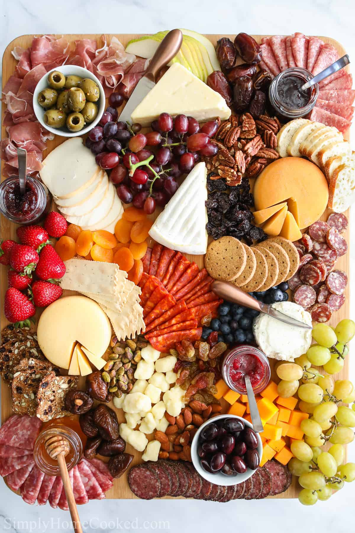 Ultimate Charcuterie Board with an assortment of meats, cheeses, fruit, nuts, bread, crackers, olives, jams, and honey.