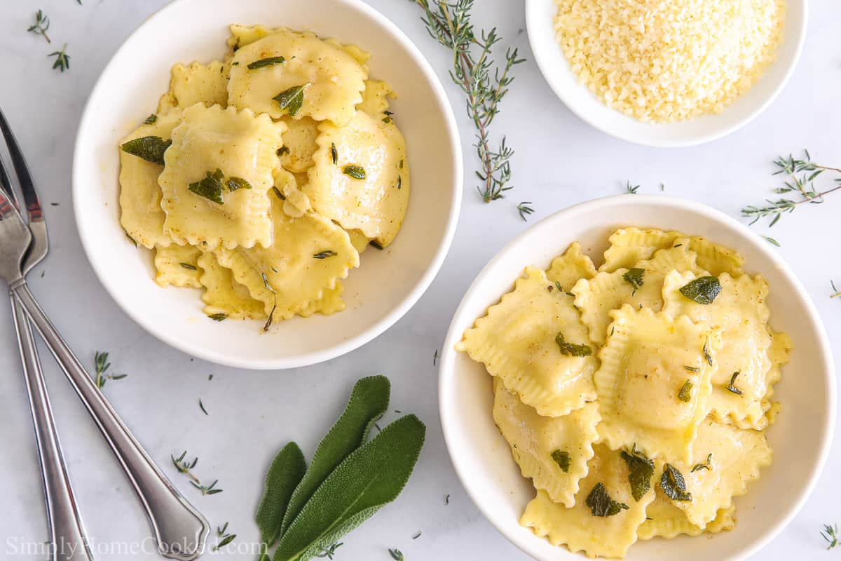 Two bowls of Butternut Squash Ravioli and a bowl of Parmesan cheese, with forks , sage leaves, and thyme on a white background.