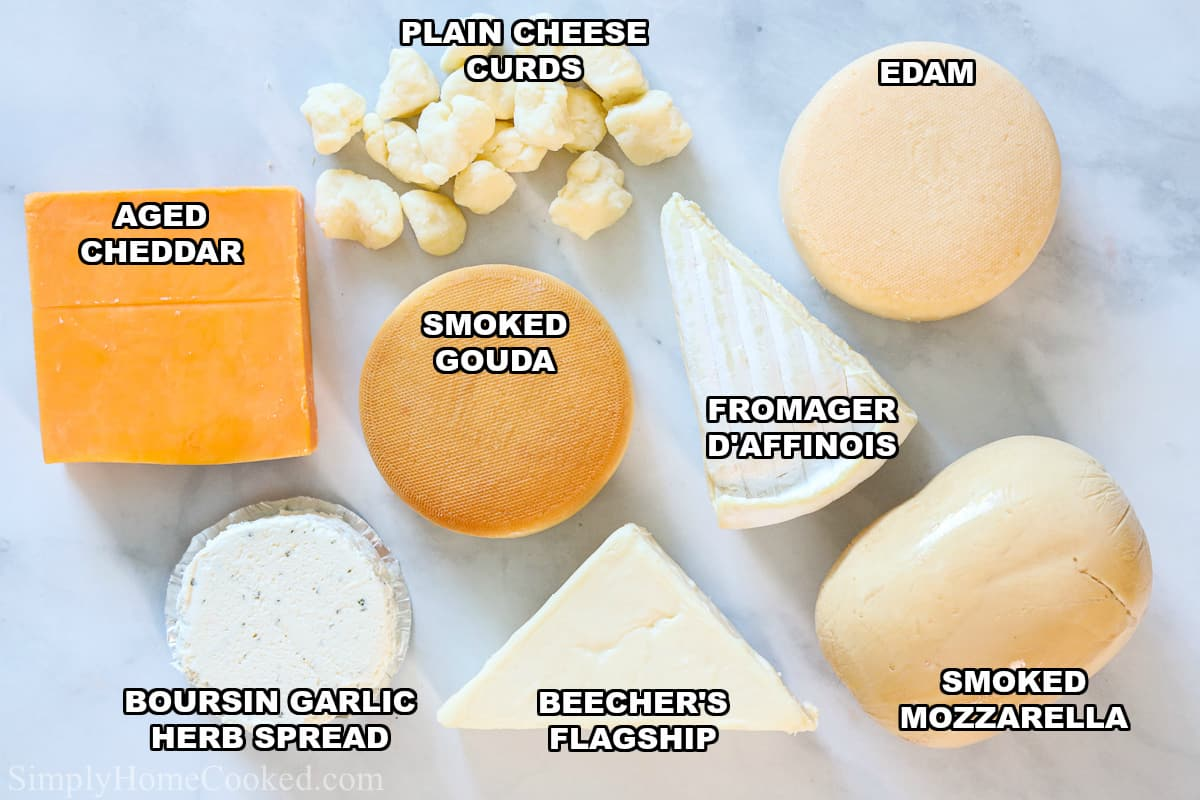 Cheeses for Ultimate Charcuterie Board, including aged cheddar, plain cheese curds, Edam, smoked gouda, fromager d'affinois, Beecher's flagship, Boursin garlic herb spread, and smoked mozzarella on a white background.