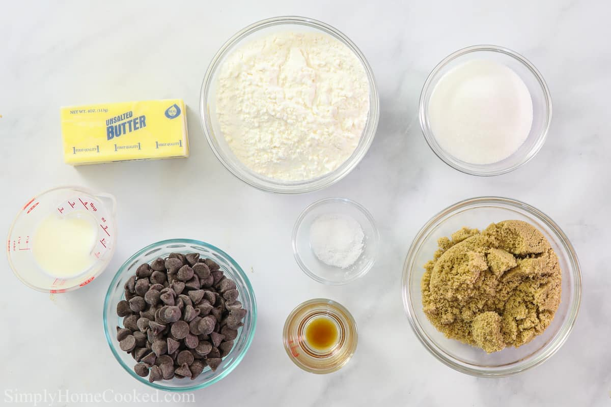 Ingredients for Quick Edible Cookie Dough, including unsalted butter, all-purpose flour, salt, milk, brown sugar, granulated sugar, vanilla extract, and chocolate chips on a white background.