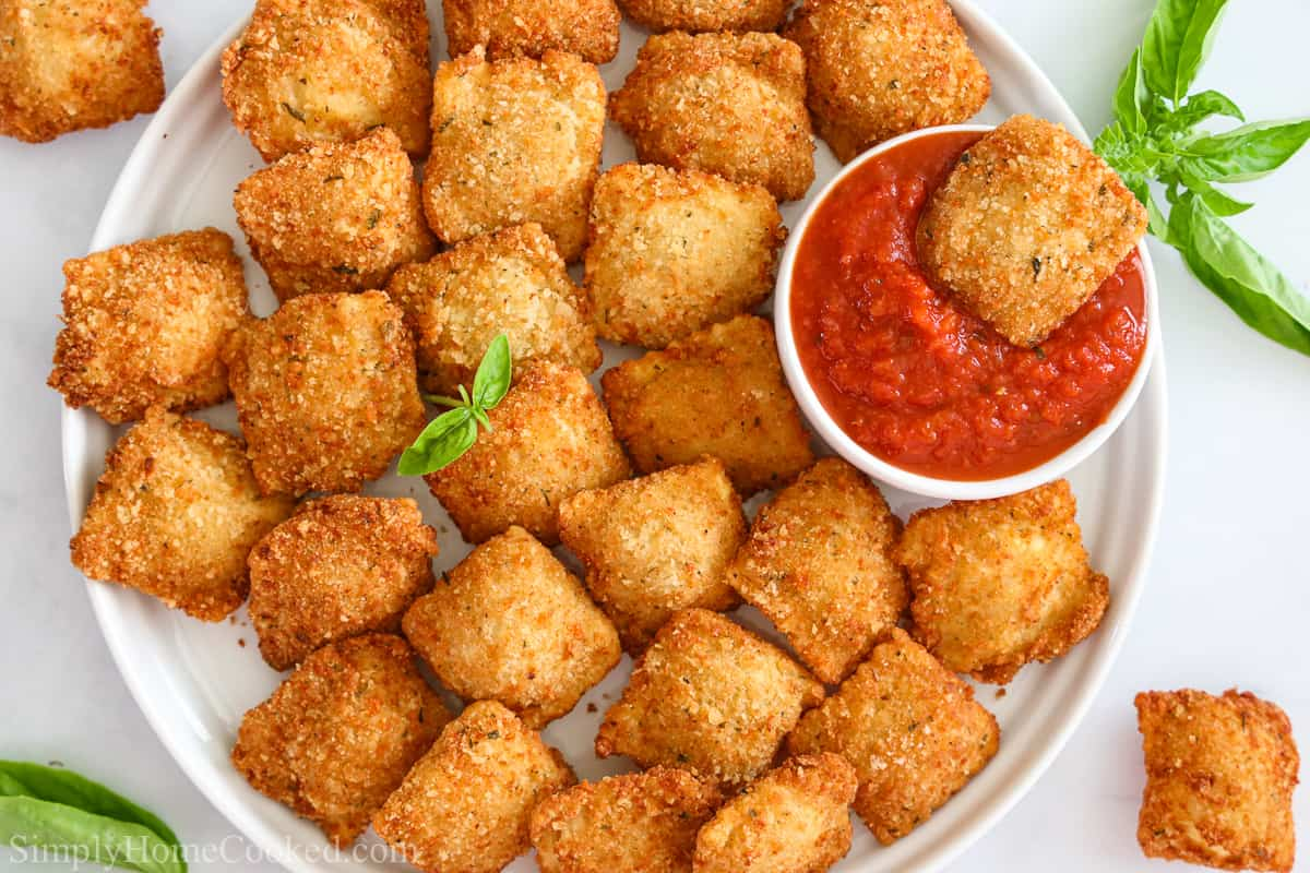 Overhead view of a plate of Crispy Fried Ravioli with one in marinara and some herbs on the side.
