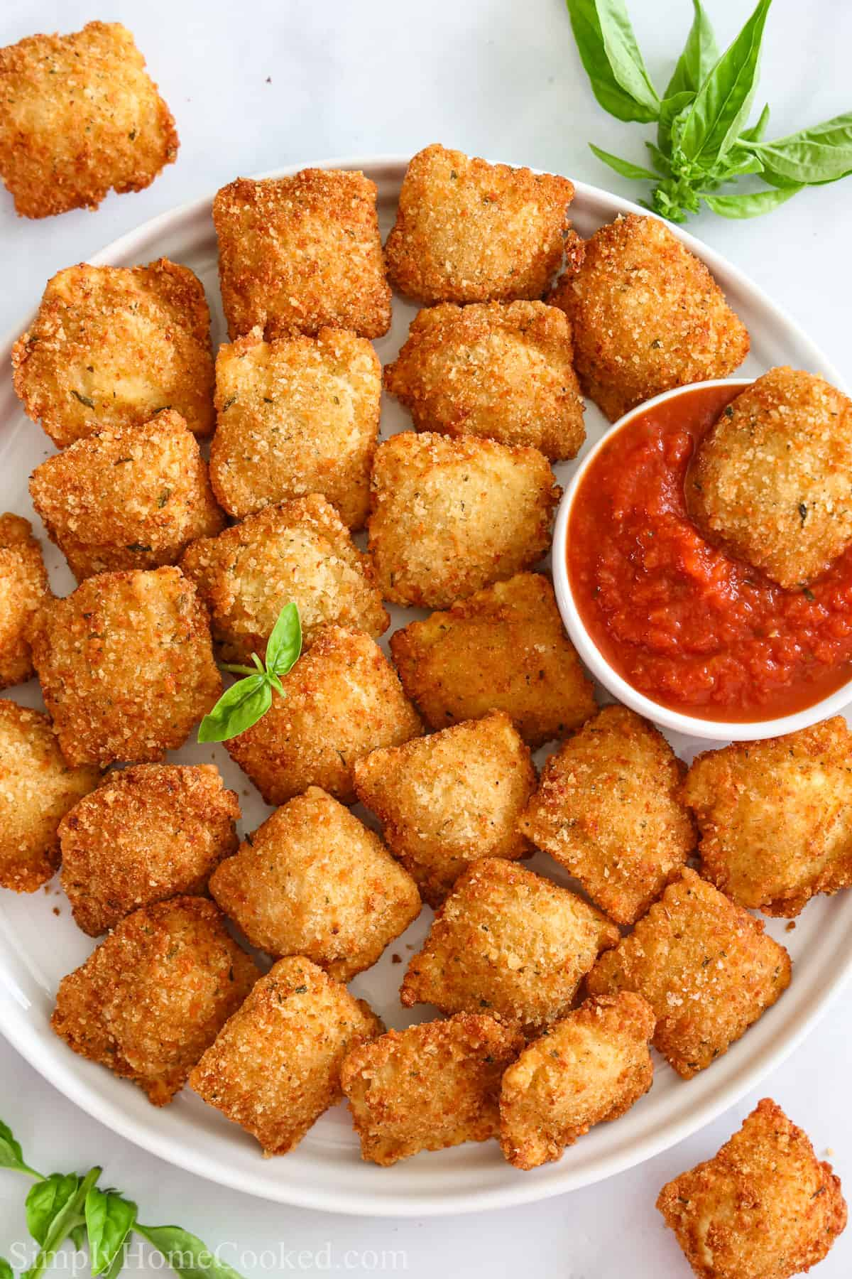 Plate of Crispy Fried Ravioli, with one in a marinara dipping sauce.