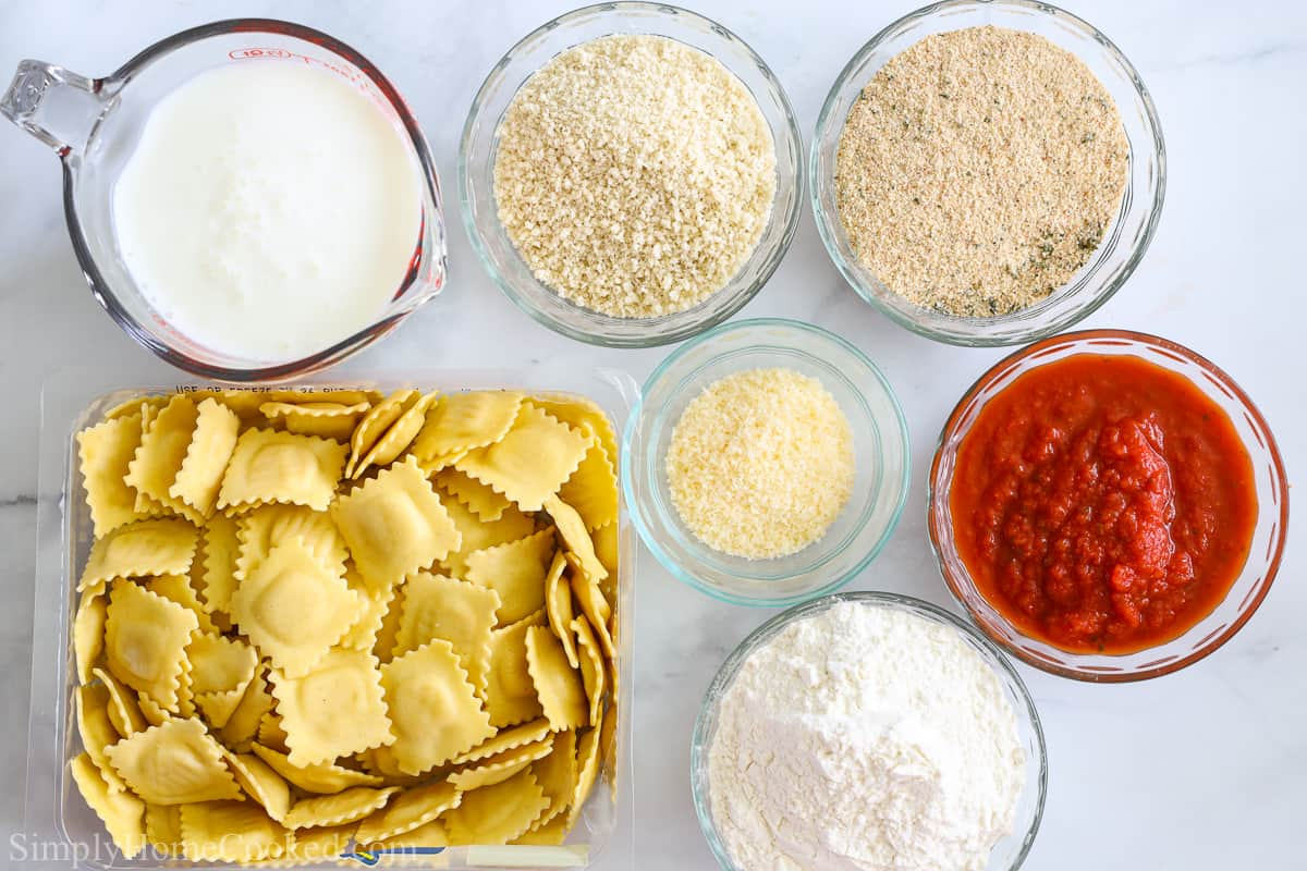 Ingredients for Crispy Fried Ravioli, including cheese ravioli, buttermilk, Italian breadcrumbs, Panko, flour, Parmesan cheese, and marinara sauce on a white background.
