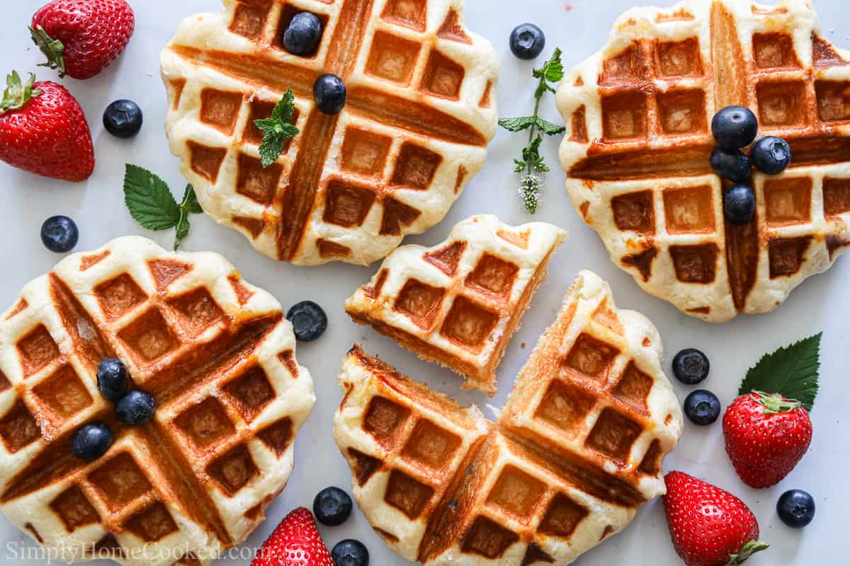 Buttery Belgian Liege Waffles scattered with blueberries, strawberries, and mint leaves on a white background.