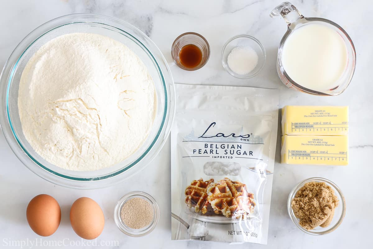 Ingredients for Buttery Belgian Liege Waffles, including flour, eggs, butter, pearl sugar, brown sugar, vanilla extract, milk, salt, and yeast, on a white background.