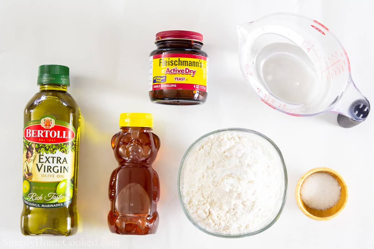 Ingredients for Zeppole Italian Donuts, including olive oil, honey, yeast, flour, water, and salt on a white background.